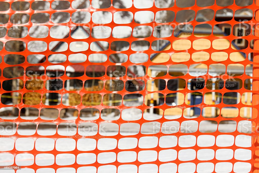 Orange snow fence in front of two defocused homes stock photo