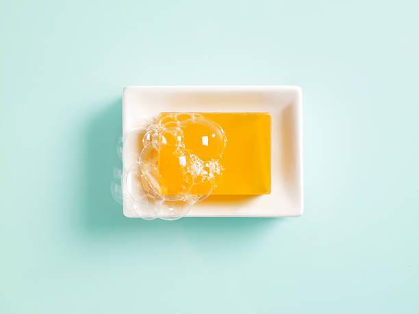 sapone in un piatto arancio - saponetta foto e immagini stock
