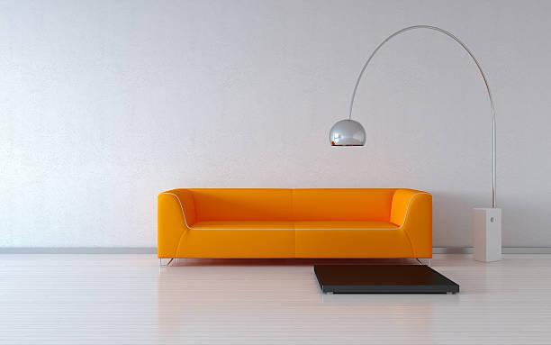 Orange sofa, lamp, empty gray wall stock photo