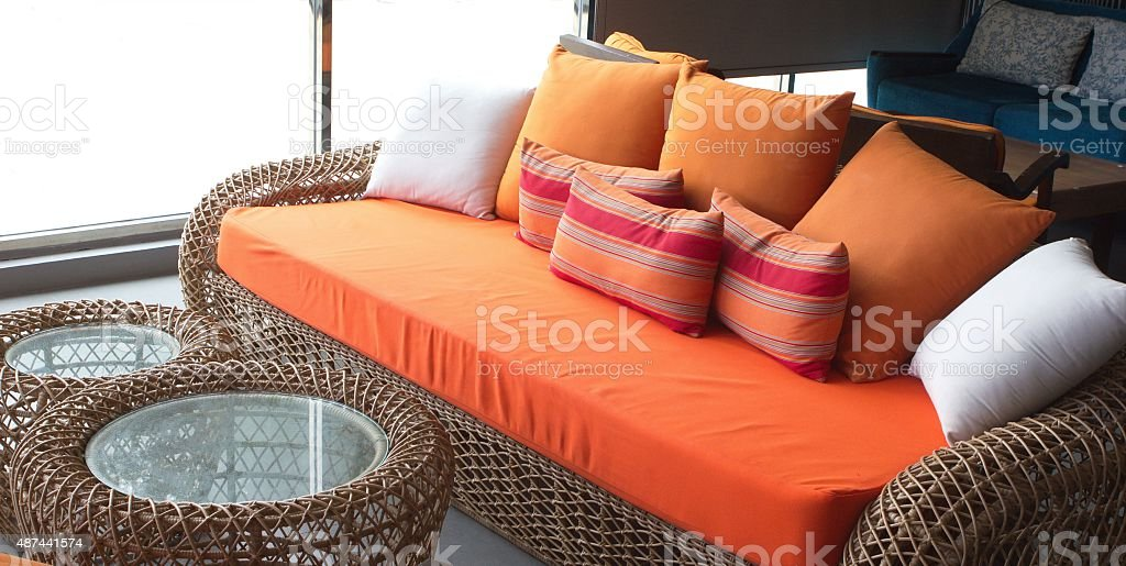 orange sofa with the colorful pillows stock photo