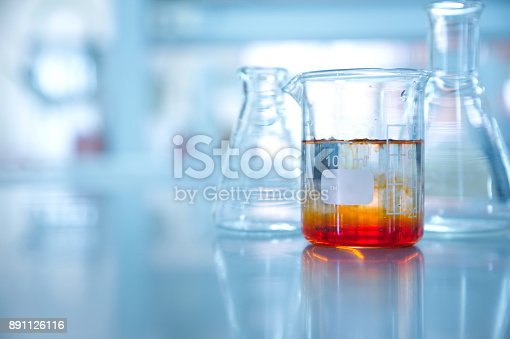 891126112istockphoto orange solution in beaker and flask in chemistry science laboratory background 891126116