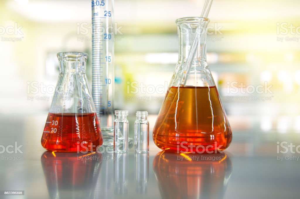 orange solution in flask cylinder vial in science laboratory background stock photo