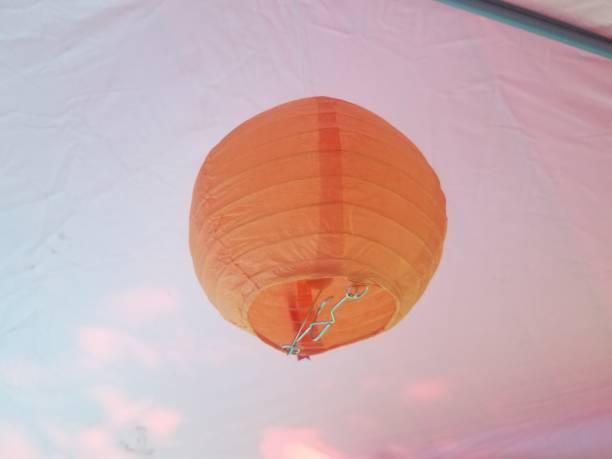 orange spherical paper lantern hanging from tent stock photo