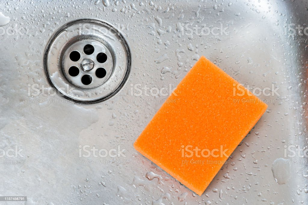 orange sponge and drain of stainless kitchen sink closeup