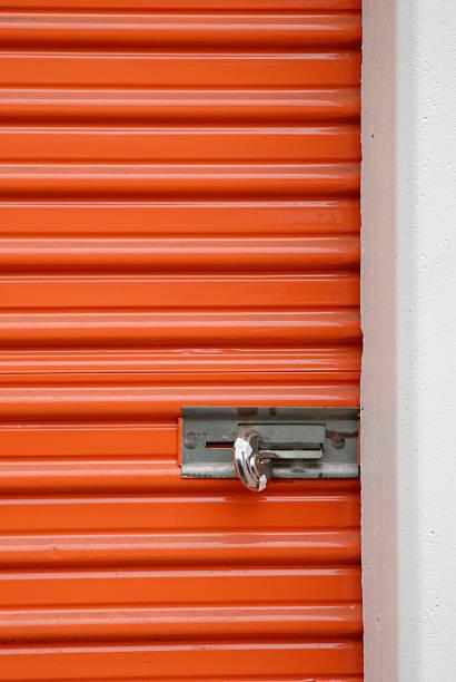 orange storage steel door with padlock stock photo