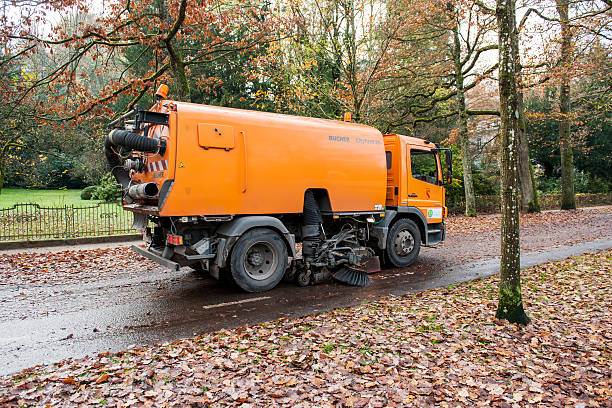 Orange street sweeper machine cleaning the street Baden-Baden, Germany - November 20, 2014: Orange Bucher CityFant 60 street sweeper machine cleaning the street after in fall from fallen foliage street sweeper stock pictures, royalty-free photos & images