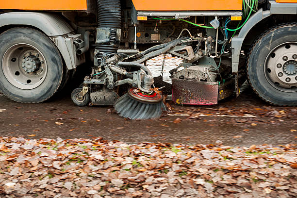 Orange street sweeper machine cleaning the street Orange street sweeper machine cleaning the street after in fall from fallen foliage street sweeper stock pictures, royalty-free photos & images