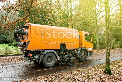 Baden, Baden, Germany - November 20, 2014: Orange Bucher CityFant 60 street sweeper machine cleaning the street after in fall from fallen foliage on a sunny day