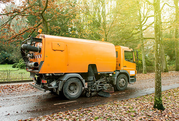 Orange street sweeper machine cleaning the street Baden, Baden, Germany - November 20, 2014: Orange Bucher CityFant 60 street sweeper machine cleaning the street after in fall from fallen foliage on a sunny day street sweeper stock pictures, royalty-free photos & images