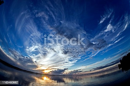 orange sun on the blue sunset sky with feathery clouds over the lake, southern Urals, lake Uvildy