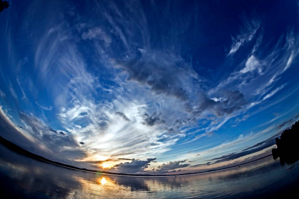 orange sun on the blue sunset sky with feathery clouds over the lake, southern urals, fish eye lens - objetiva olho de peixe imagens e fotografias de stock