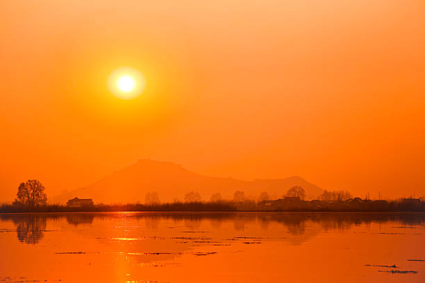 Orange sun over serene lake stock photo