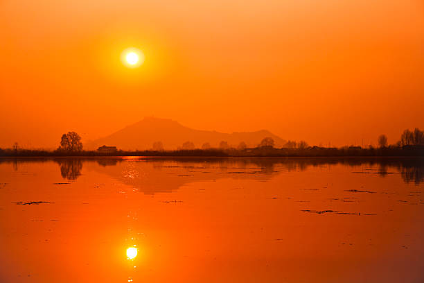 Orange sun over serene lake with reflection stock photo