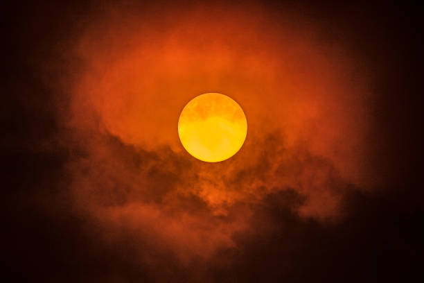 Orange sun through thick smoke from out of control bush fire stock photo