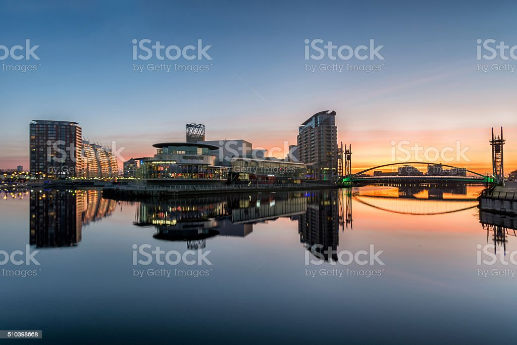 Orange Sunrise At Salford Quays With Reflections. A winter orange sunrise at Salford Quays with clear reflections in the water. Apartment Stock Photo