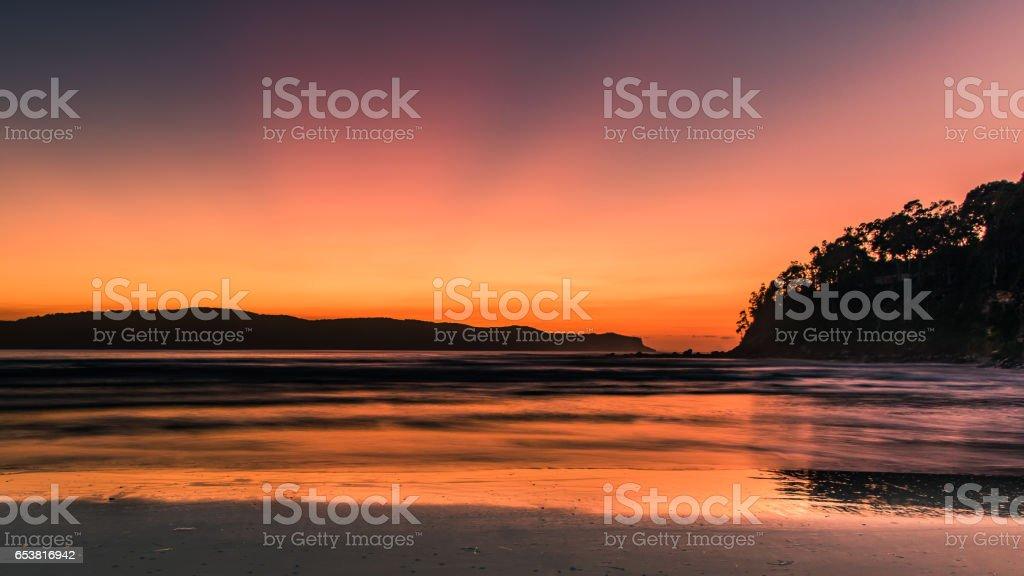 Orange Sunrise Seascape with Silhouettes stock photo