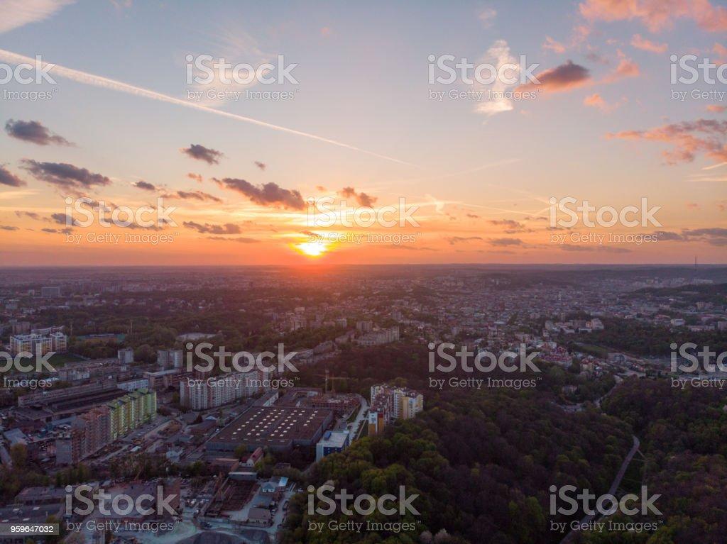 naranja puesta de sol sobre la ciudad. vista aérea. copas de los árboles - Foto de stock de Aire libre libre de derechos