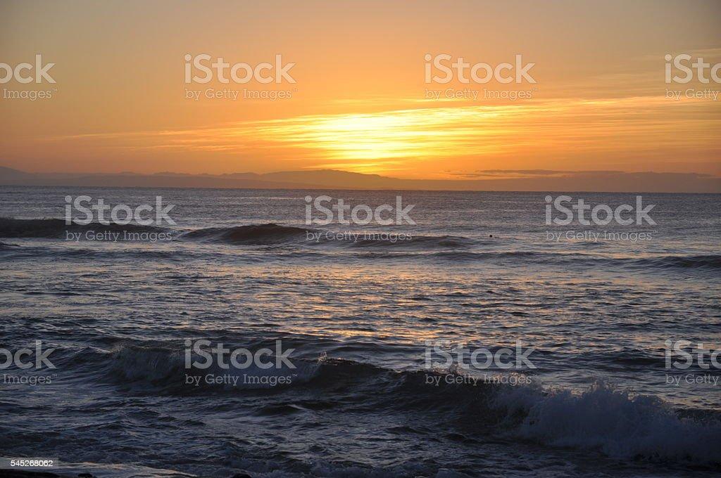 Orange sunset behind island with waves stock photo