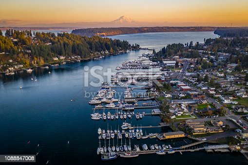 A drone view of boats in Gig Harbor Washington at sunset with Mt Rainier