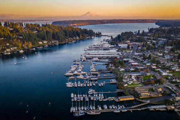 Orange Sunset Glow Over Gig Harbor Washington Aerial A drone view of boats in Gig Harbor Washington at sunset with Mt Rainier puget sound stock pictures, royalty-free photos & images