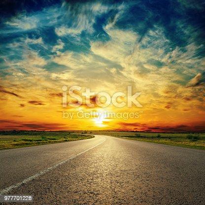 orange sunset in low dramatic clouds over asphalt road