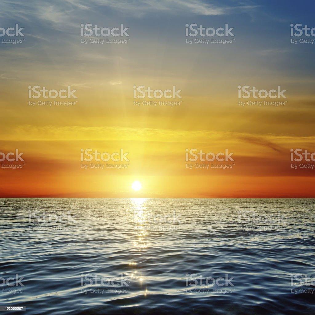 orange sunset over dark blue sea stock photo