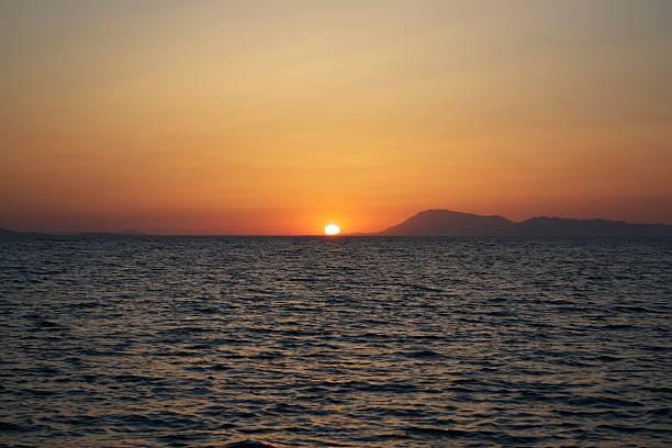 Orange sunset over turkish waters stock photo