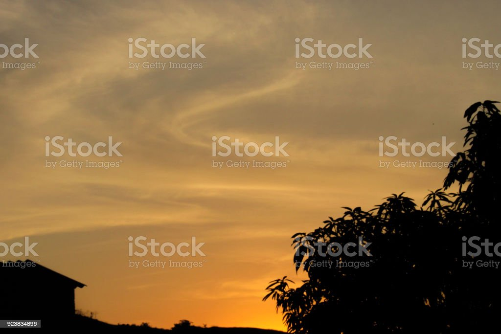 Orange sunset with house and tree silhouette stock photo