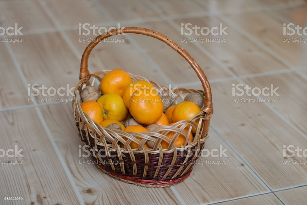 orange tangerines and walnuts in a basket on the floor royalty-free 스톡 사진