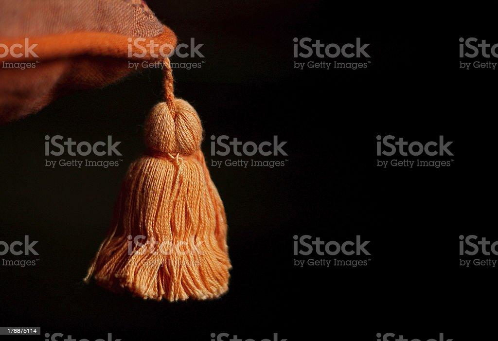 Orange tassel on black royalty-free stock photo