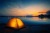 istock Orange tent on the lake at dusk 1222972663