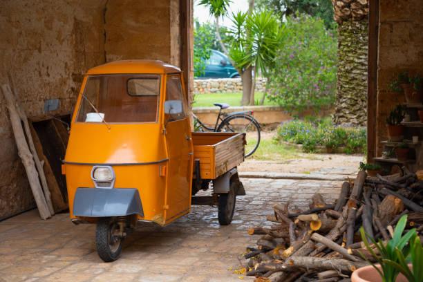 Orange three wheels car used for transporting - foto stock