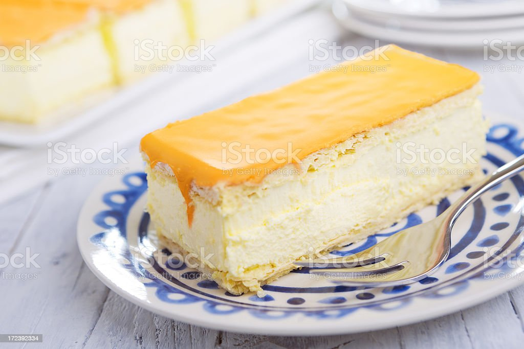 Orange tompouce, traditional Dutch pastry, on a rustic table royalty-free stock photo