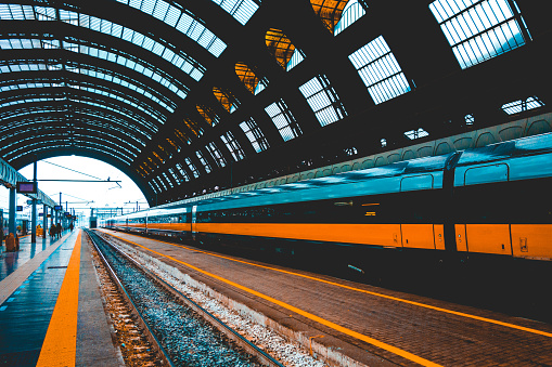 orange train in a central station at italy