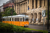 Budapest, Hungary - may 06 2019: Orange Tram on square between the building of parliament and ethnographic museum in Budapest. Budapest is a capital of Hungary.
