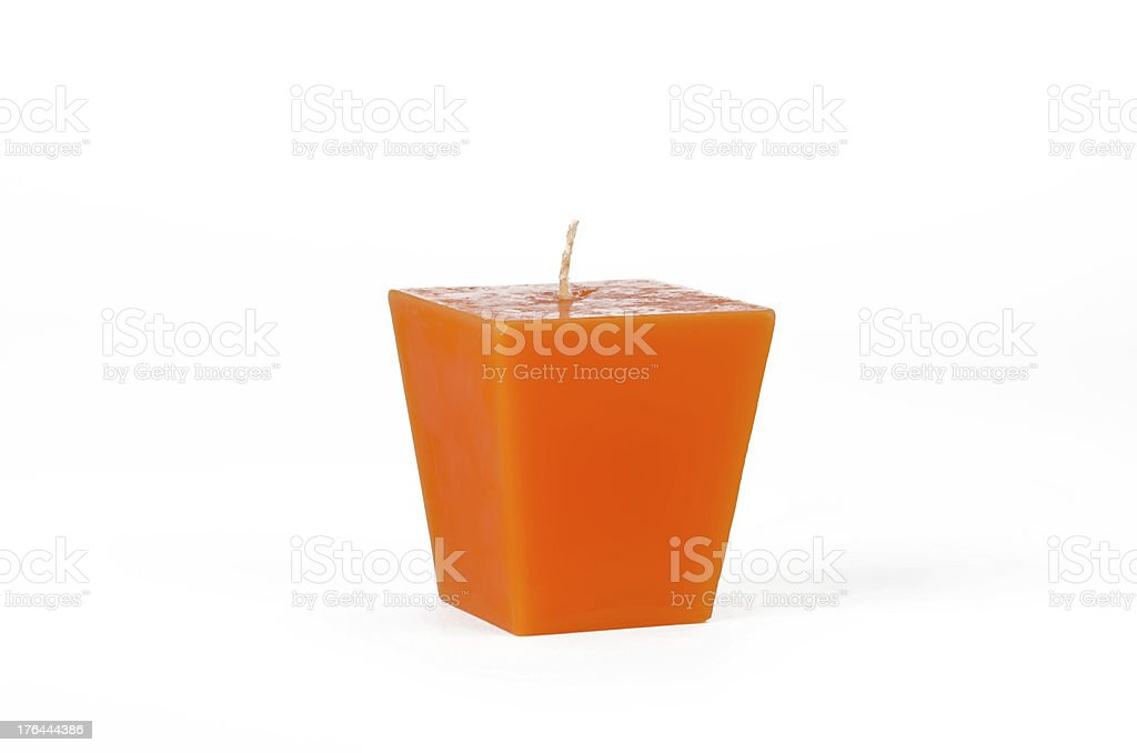 Orange trapezoid candle with a wick stock photo
