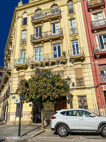 Valencia, Spain - December 8, 2020: Orange tree with fruits in the street in front of beautiful classical building. It is not unusual to see this all over southern Spain
