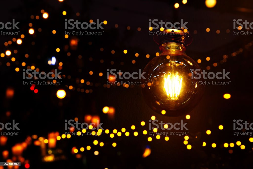 orange tungsten retro lamp with bokeh line of light party in bar or club dark night background stock photo