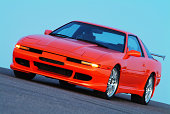 """Tangelo orange, turbocharged sports car/tuner car with 18-inch wheels, body kit and aluminum wing. Fuji S2 Pro, 80-200mm lense, tripod."""