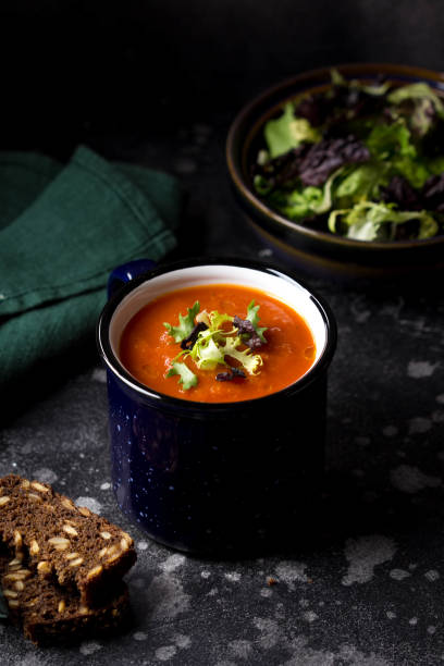 Orange vegetable cream soup in mug (tomato, carrot, lentil, pumpkin), delicious hot homemade lunch in cup. Dark background Red vegetable cream soup in blue mug (tomato, carrot, lentil, pumpkin), delicious hot homemade lunch in cup. Dark background vegetable soup stock pictures, royalty-free photos & images