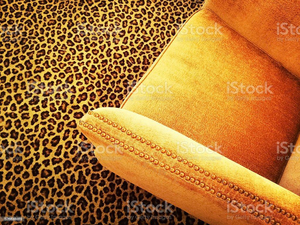Orange velvet armchair on leopard carpet stock photo