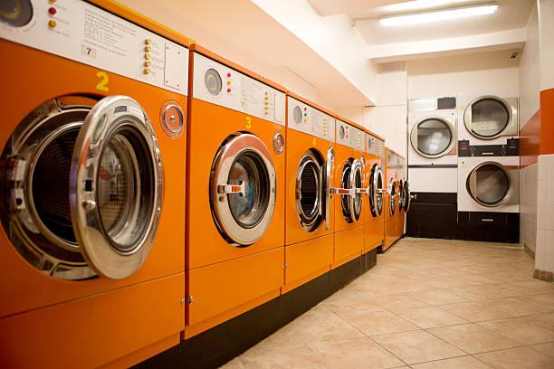 Orange washers at a laundromat stock photo