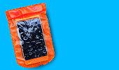 青の背景に分離された水滴付きオレンジ防水携帯電話ケース。PVC ジップロックバッグは、水から携帯電話や重要なアイテムを保護します。タイのソンクラーン水祭りのコンセプト。
