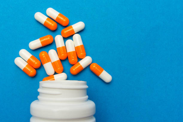 orange white capsules (pills) were poured from a white bottle on a blue background. medical background, template. - antibiotico foto e immagini stock
