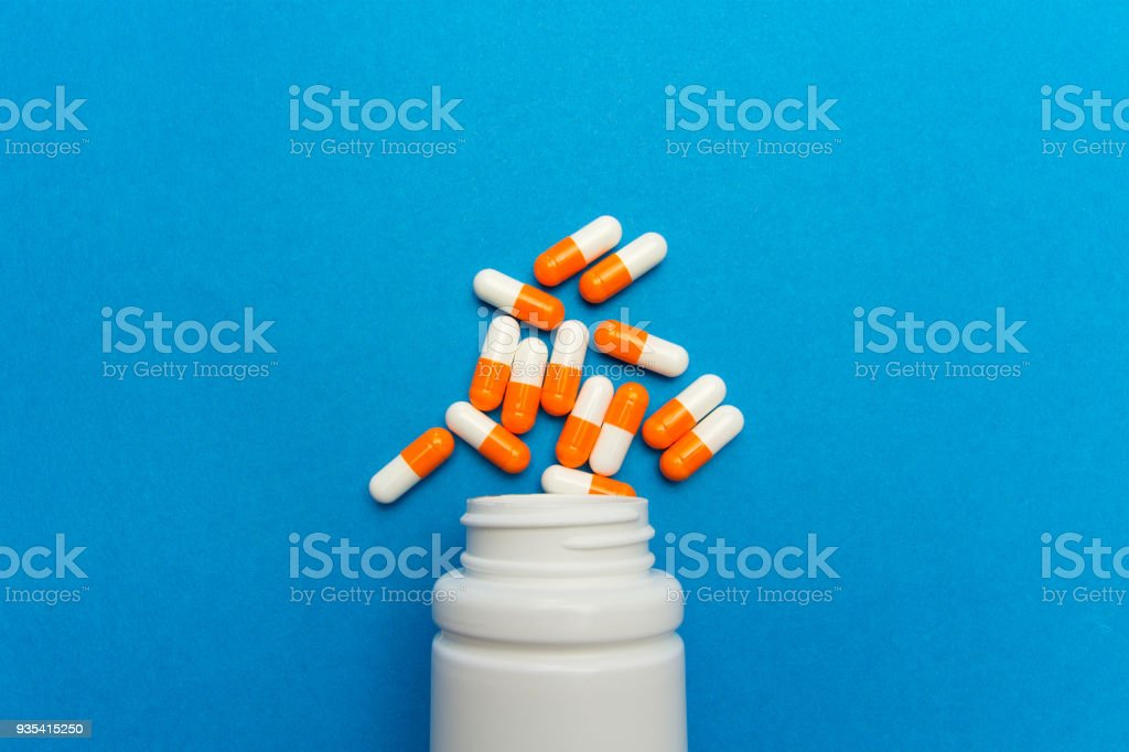 Orange white capsules (pills) were poured from a white bottle on a blue background. Medical background, template. stock photo