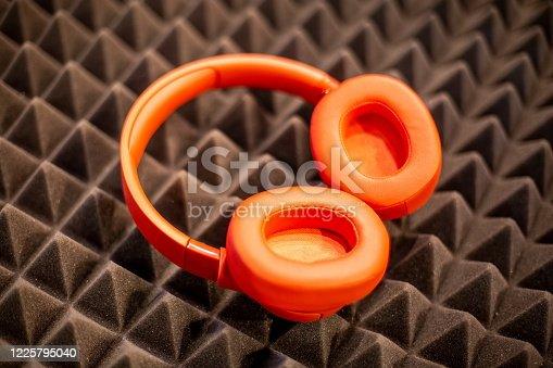 orange wireless overhead monitor headphones lie on a dark foam rubber noise canceling panel. close-up soft focus, blur background