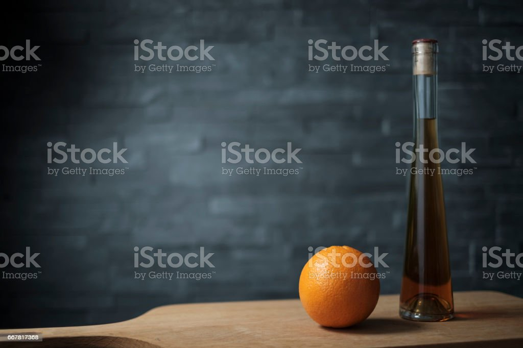 orange with a bottle of liquor on a wooden plank stock photo