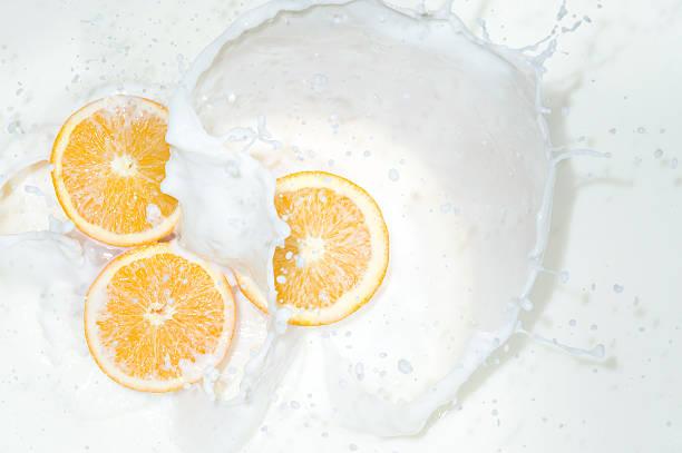 Naranja con salpicaduras de leche - foto de stock
