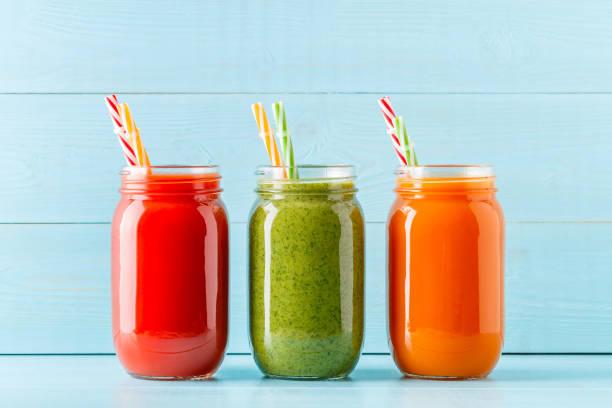 orange/grün/rot gefärbt smoothies / saft in einem glas - einmachglassmoothie stock-fotos und bilder
