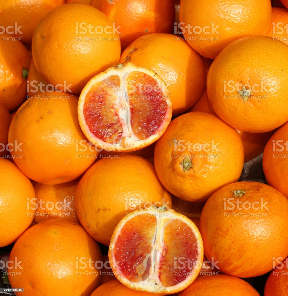 oranges and an orange cut in the stall of greengrocer stock photo